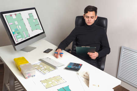 Architect at work. Guy is architect in his office. He works with architectural drawings. Construction drawings development concept. Creation of building plans. Architectural bureau office