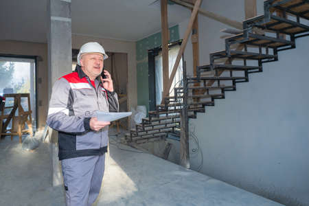 Construction team foreman. Builder is talking on phone. He holds documents in his hands. Builder inside a building under construction. Concept - he calls customer. Foreman calls contractors.