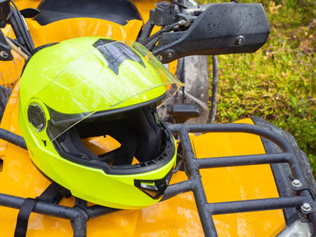 ATV helmet close up. Yellow protective ATV helmet. Concept is safety during motocross. ATV driver's head protection. Driver's head hemlet quad cycle. Equipment for extreme sports.
