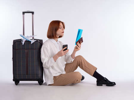 Traveler sits next to suitcase. Airplane model as symbol of air travel. Woman holding plane tickets and phone. Female traveler a white background. Portrait of a girl traveler dressed in casual style