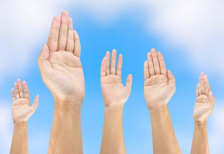 raise hand: people raise hand on sky background