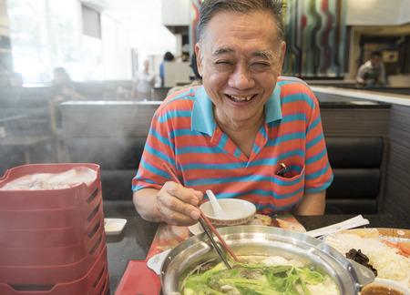 Boldog öregember eszik egy shabu shabu (hot pot)