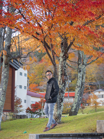 find similar images: Preview Save to a lightbox  Find Similar Images  Share Stock Photo: a man relaxing with a beautiful Japan , Nikko autumn tree . focus on the model . Japan autumn set Stock Photo