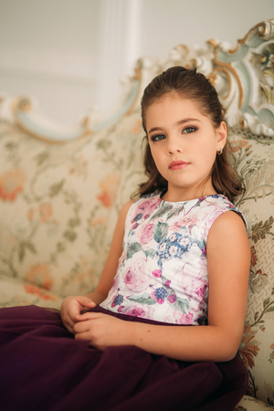 Schöne Mädchen in einem lila Kleid und Blume Bluse posiert für einen Fotografen. Photosession für die Zeitschrift.