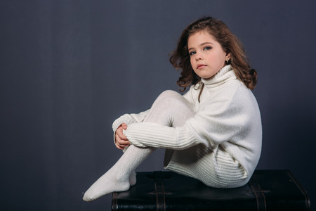 Little beautiful girl with brown hair in a light sweater. Studio. A princess.