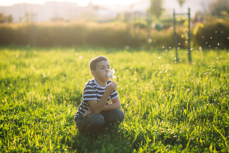 see through: A little boy in a striped T-shirt is smiling and cheering.Spring, sunny weather. Stock Photo
