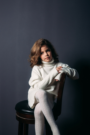 Little beautiful girl with brown hair in a light sweater and with a skirt of tulle.Studio. A princess poses for a photographer.