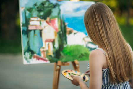 Das blonde Mädchen malt mit Hilfe von Farben ein Gemälde auf die Leinwand. Eine hölzerne Staffelei hält das Bild. Sommer- Standard-Bild - 81119539