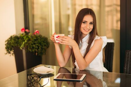 Young girl use a tablet and phone to work. The girl in the cafe is smiling. summer sunny day Stock Photo