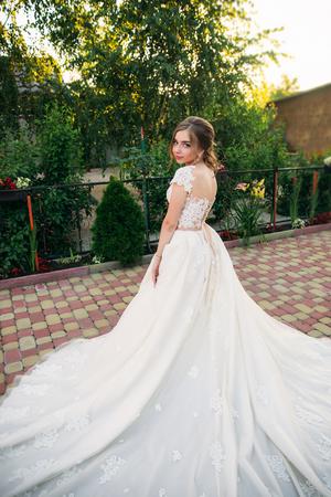 公園のカメラマンのポーズでウェディング ドレスの少女。晴れた日、夏。