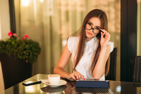 Business lady uses a tablet and phone to work. The girl in the cafe is smiling. Summer
