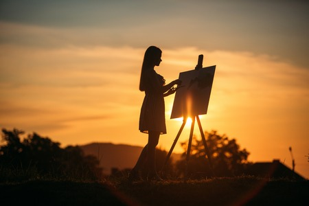 Silhouette of blonde girl paints a painting on the canvas.Palette with paints and spatula, summer sunny day