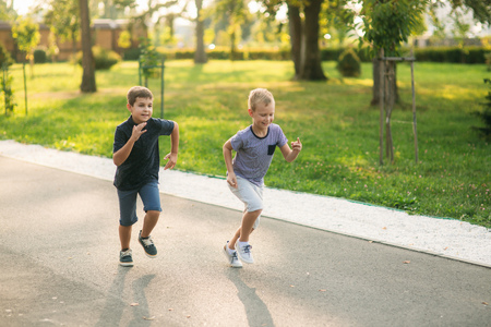 Two children are playing in the park. Two beautiful boys in T-shirts and shorts have fun smiling. They eat ice cream, jump, run. Summer is sunny Standard-Bild