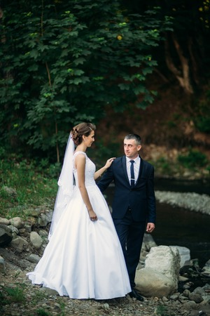 Young couple, bride and groom walking and enjoying their wedding day. Sunshine. Summer