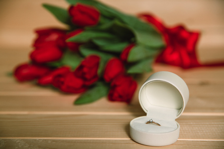 Bouquet of red tulips and diamond ring for marriage