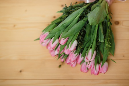 Bouquet of pink tulips and  with a beautiful bow on a wooden background Stock Photo