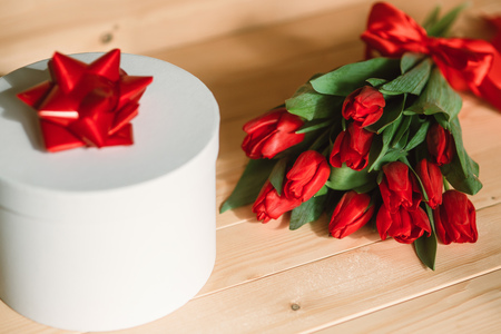 Beautiful red tulips with a gift. Red bow on a gift on a wooden background Stock Photo