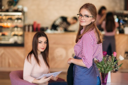Mid section of waitress taking order at restaurant Stock Photo
