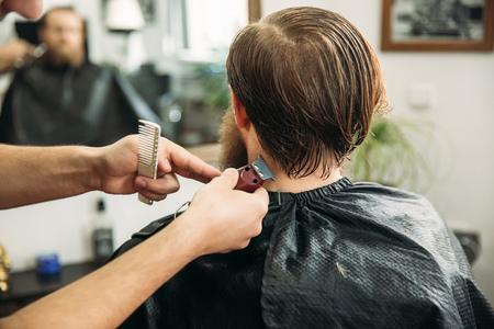 Bearded man having a haircut with a hair clippers