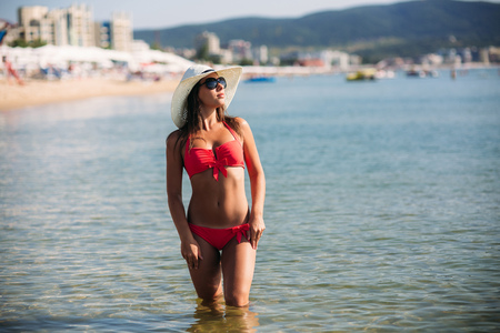 Beautiful girl in a pink bathing suit, in the sea. Sunny weather. Summer Фото со стока