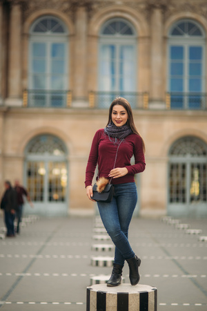 A beautiful girl in burgundy golf with a gray scarf stands on a striped dais. The girl smiles and rejoices Reklamní fotografie