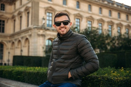 Handsome man in a khaki jacket and sunglasses is sitting on bard Stock Photo