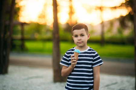 A little boy in a striped T-shirt is eating blue ice cream.Spring, sunny weather