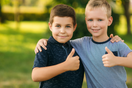 Two children are playing in the park. Two beautiful boys in T-shirts and shorts have fun smiling