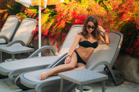 Beautiful lady lies on the longer in black bathing suit