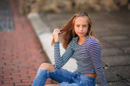 young teenage poses for photo. blonde girl in jeans and blouse. play with hair