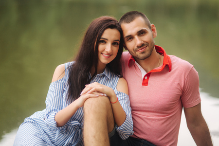 Beautiful couple walking in the park near the lake, sit on the pier Stock Photo