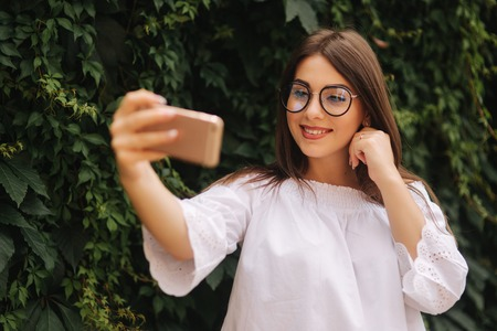 Happy beautiful girl using smart phone in the city, summer girl portrait