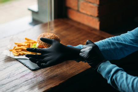 Man in black gloves takes a burger in his hands