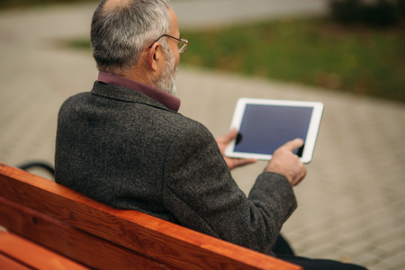 Grandpa uses a tablet sitting in the park on the bench