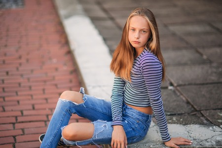 young teenage poses for photo. blonde girl in jeans and blouse