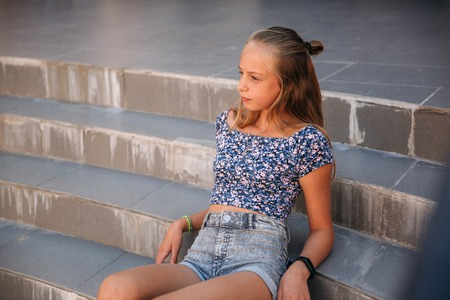 teenage female dressed in jeans sits on stairs