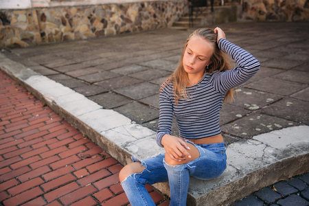young teenage poses to photographer. blonde girl in jeans and blouse