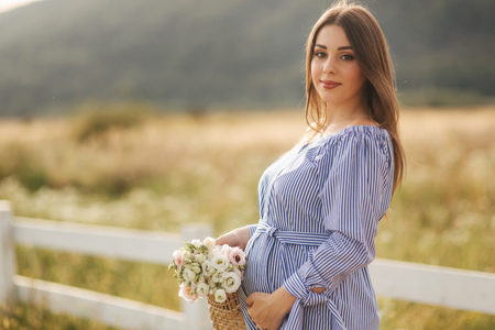 Close up view of beautiful pregnant woman in field holding bouquet and smile. Relax in nature. She put her hand on her belly Archivio Fotografico