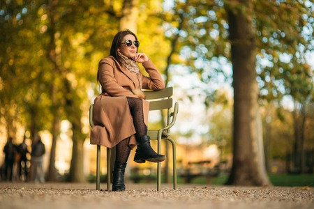 A young girl in a brown coat sits in the middle of the park on a khaki stool. Reklamní fotografie