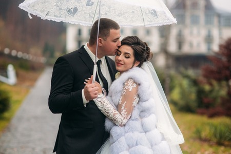 Groom and bride walking in the park on their wedding day. Autumn weather. Rair. Couple umbrella