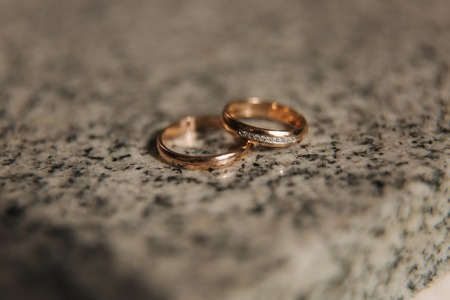Wedding rings on table. Gold rings with diamond on sun. Wedding accsessories. macro Reklamní fotografie