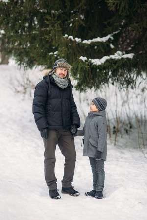 Happy father with his son walks through the park in the snowy winter weather