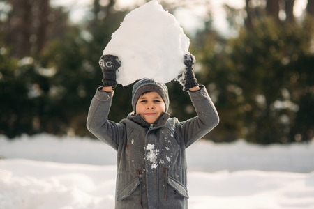 Little Boy play with snow. He take a snowballs and play Stok Fotoğraf
