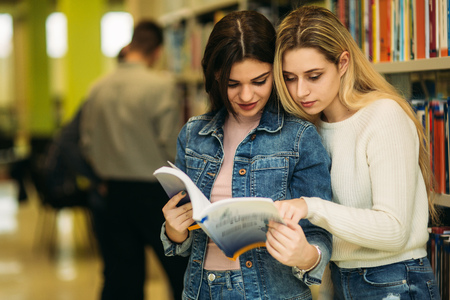 Group of student want to find some helpful literature to preparing for university exam. Two girl find some interestin information about boys Stok Fotoğraf