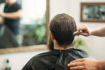 Male client with wet head getting haircut by hairdresser in barber shop