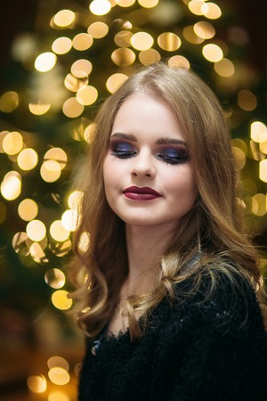 Smiling girl with beautiful makeup in front of christmas tree