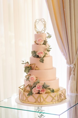 Beautiful wedding cake decorated with flowers. Pink color of cake. Powder rose Standard-Bild