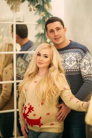 Happy couple stand near the mirror in Christmas time. Holliday spirit Stock Photo