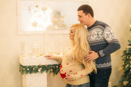 Happy couple in holiday spirit. Yong fimily in beautiful knitted sweaters in anticipation of Christmas holidays