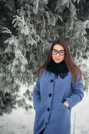 Beautiful happy young woman with black glasses wearing winter coat color Blue Cobalt and black scarf covered with snow flakes